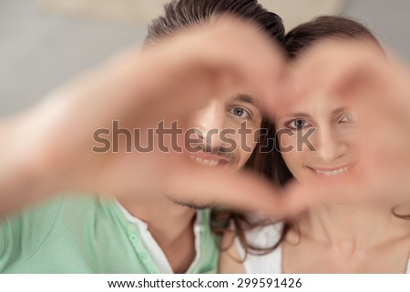 Close up Sweet Young Couple Looking at the Camera Through Hands Forming Heart Shape with Smiling Faces. - stock photo