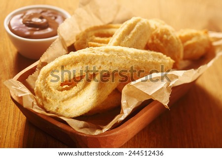 Close up Tasty Churros Snacks on Tray, with Paper, Placed on Wooden Table with Chocolate Dipping Sauce. - stock photo