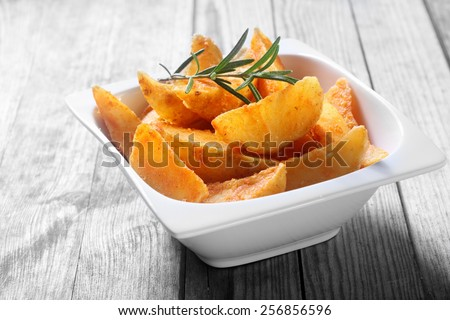 Close up Tasty Fried Potato Snacks on White Bowl on Top of Wooden Table - stock photo