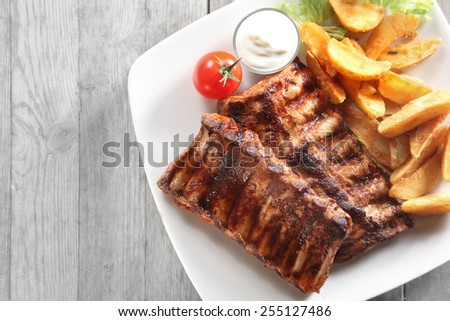 Close up Tasty Grilled Pork Rib and Fried Potatoes on White Plate with White Sauce on a Plate. Placed on Wooden Table With Copy Space. - stock photo