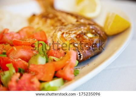 close-up teeth of grilled red snapper served with mixed vegetables and lemon