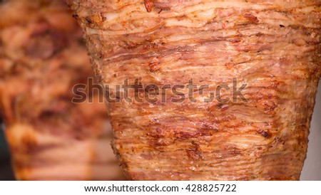 Close up texture of  rotating skewered chicken, pork and lamb meat grilled and ready to serve in a typical Greek sandwich called gyros or Turkish doner kebab. - stock photo