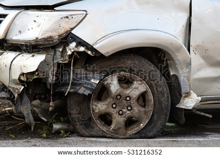 Close up the front tires and the car, which was demolished in the collision severely damaged by the accident.
