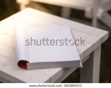 Close up the white book on the table in garden with sun light