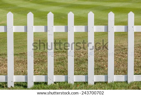 Close up the white wooden fence with green meadow background. - stock photo