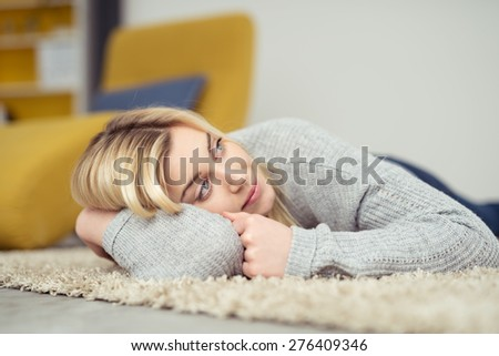 Close up Thoughtful Blond Girl Lying on the Carpeted Floor at the Living Room, Leaning on her Arm and Looking Up - stock photo