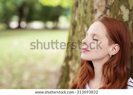 Close up Thoughtful Pretty Young Woman Leaning her Back Against the Tree Trunk at the Park with With Eyes Closed. - stock photo