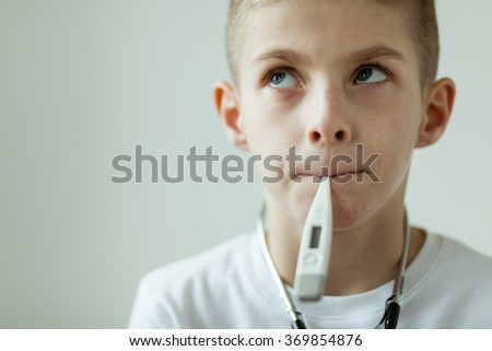 Close up Thoughtful White Boy with Digital Thermometer in his Mouth Looking up Seriously Against White Wall Background. - stock photo