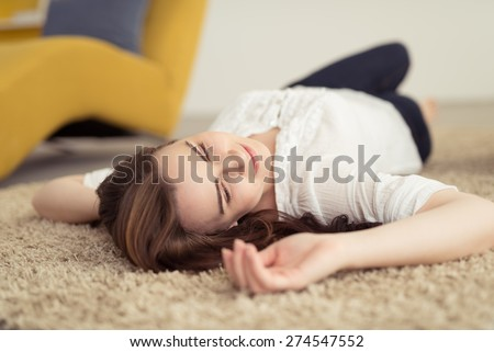 Close up Thoughtful Young Attractive Woman Lying Down on the Floor with Carpet While looking to the Right of the Frame - stock photo