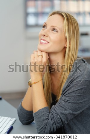 Close up Thoughtful Young Office Woman Sitting at her Desk, Looking Up with Hands on her Chin, Showing Happy Facial Expression. - stock photo