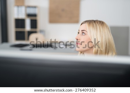 Close up Thoughtful Young Office Woman with Blond Hair Looking to the Upper Left Side of the Frame While Sitting at her Workplace. - stock photo