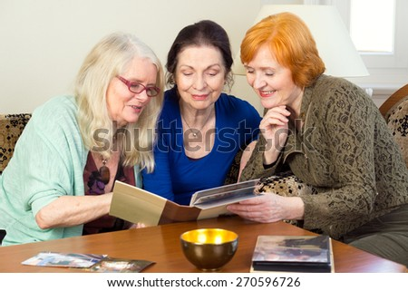Close up. Three Middle Age Female Friends Sitting at the Living Area Looking at Photo Album Together and Talking Happy Moment in the Past. - stock photo