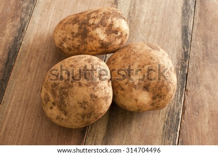 Close up Three Unwashed Fresh Potatoes on Top of a Wooden Table. - stock photo