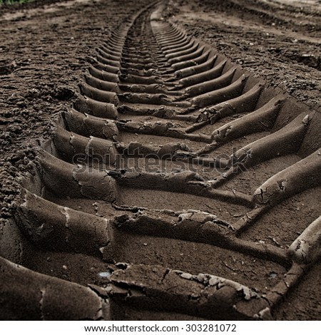 Close-up tire tracks truck on a dirt road in daylight - stock photo