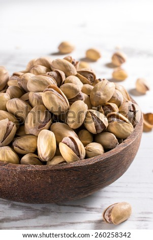 Close up to pistachios in the wooden bowl,selective focus  - stock photo