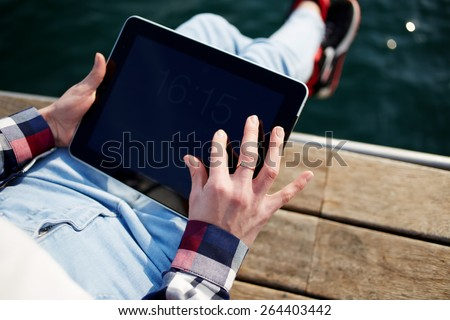 Close up to view young woman's hands hold black tablet with empty blank screen, female hands holding touch screen tablet pc while relaxing on wooden jetty at lake, woman relaxing at sony day outdoors - stock photo