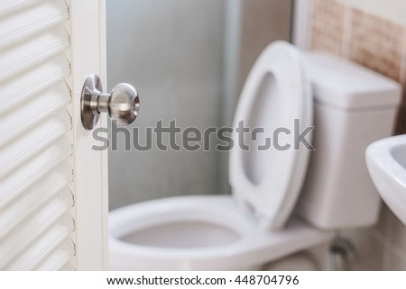 Close up, toilet door opening, with stationery ware, selective focus on door knob - stock photo