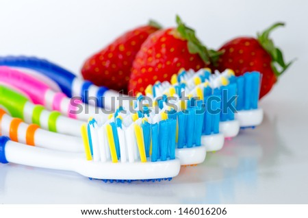 Close up toothbrush and strawberry isolated - stock photo
