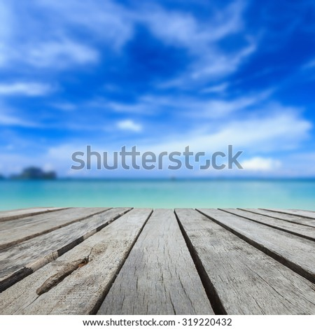 Close up top of wood table and view of sea and blue sky - stock photo