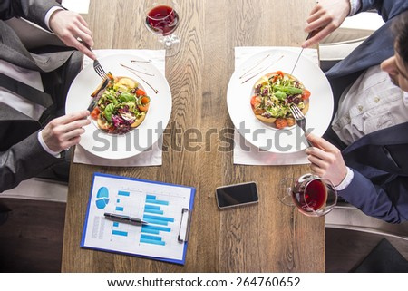 Close-up. Top view. Businessmen eating during a business lunch in restaurant. - stock photo
