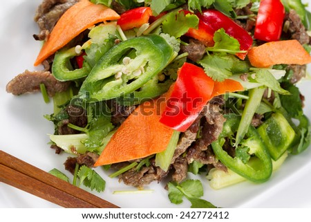 Close up top view image of Chinese meat and vegetable dish with chopsticks on side  - stock photo