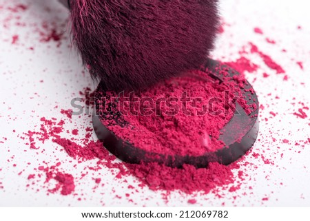 Close-up top view of  natural  black bristle of professional  make-up brush with crashed pink eyeshadow in opened single pink eye shadow  pot  isolated on white background