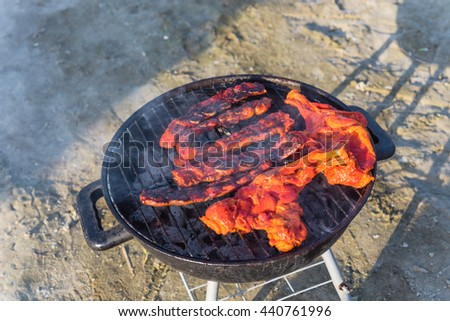 Close-up, top view of pork and meat skewers being grilled in a barbecue on the beach. Food, summer, beach and leisure concept. Picnic, outdoor, camping, dinner on summer beach. Grill barbecue cookout.