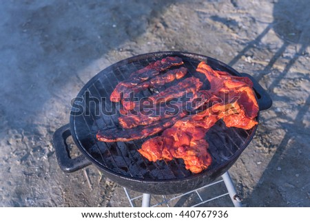Close-up, top view of pork and meat skewers being grilled in a barbecue on the beach. Food, summer, beach and leisure concept. Picnic, outdoor, camping, dinner, cookout on summer beach. Vintage filter