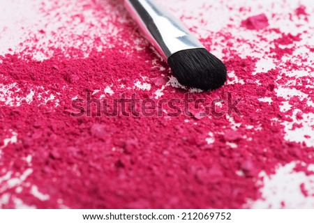 Close-up top view of  professional  make-up brush with natural  black bristle,  black ferrule, with crashed pink eyeshadow isolated on white background