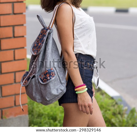 Close up torso of young brunette woman in sexy denim shorts and white T-shirt, with a bag over arm of standing at a brick wall in the city travel, vacation tanned beautiful figure  - stock photo