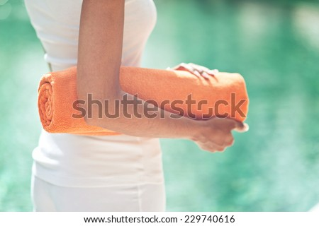 Close up torso view of a slender young woman standing poolside with a rolled towel against sparkling cool blue water in a wellness and spa concept - stock photo