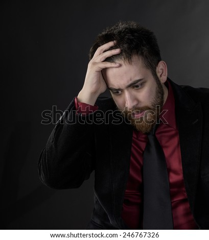 Close up Troubled Goatee Young Man in Black and Maroon Formal Wear. Captured on Gray Background