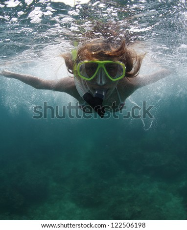 Close up underwater portrait of a woman in mask making bubbles