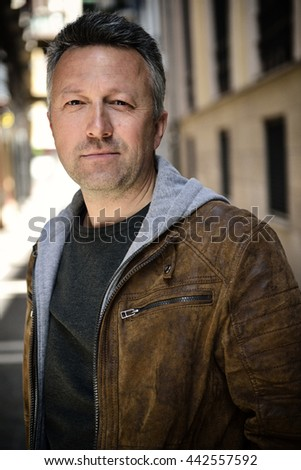 Close-up urban outdoor portrait of a handsome man, image toned and noise added - stock photo