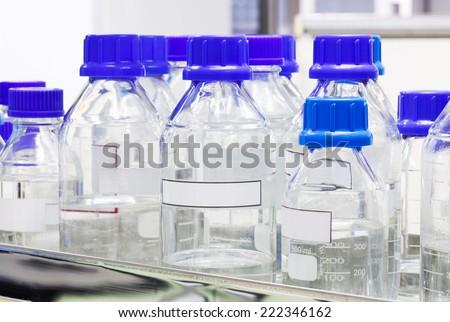 Close up varieties size of laboratory glass bottle on shelf - stock photo
