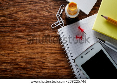 Close up Various Educational Supplies and Mobile Phone Gadget on Brown Wooden Table with Copy Space for Texts on the Left Side. - stock photo