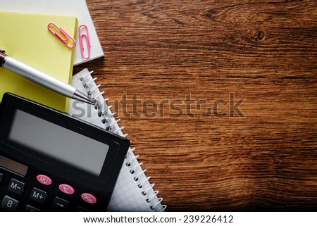 Close up Various Office Supplies on Wooden Table, such as Calculator, Papers, Notes, Pen and Clips, Captured on the Left Edge of the Frame with Copy Space for Texts on Right Side. - stock photo