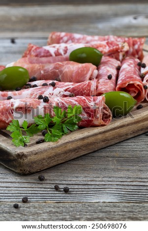 Close up vertical image of various meats on serving board with ham, pork, beef, parsley, and olives on rustic wood. Focus on front top part of serving board and first row of meat.  - stock photo