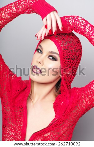 Close-up vertical portrait of beautiful woman wearing red clothes with make-up on the face looking at the camera - stock photo