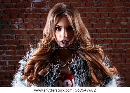 close-up, very cute sexy young girl or woman with long curly hair and fashion make-up in jeans shorts and red T-shirts, in darkness on a background of a brick wall, copy space for text
