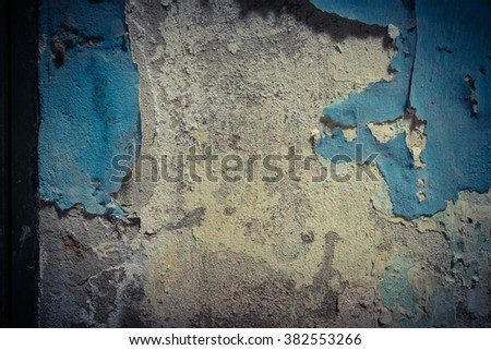 Close-up view a weathered damaged concrete wall with blue peeling paint and cracked stucco layer. Pattern of rustic blue grunge material from old wall seamless texture in an ancient town of Vietnam.