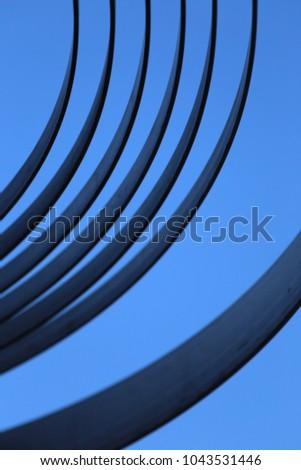 Close up view from bellow of iron decorative curved elements. Blue sky in background. Circular lines silhouettes. Geometric abstract image. Pattern of grey metallic arcs and semi circles. Urban image.