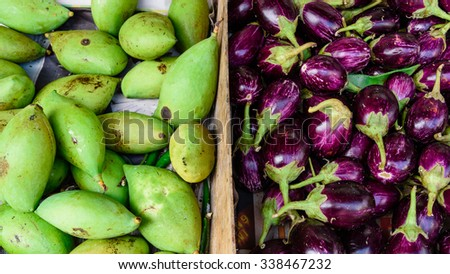 Close-up view group of fresh organic raw green Mangoes and Eggplant (or Brinjal) on display at Vegetable and Fruit Stall of Local Market at Little India, Singapore. Colourful and healthy concept - stock photo