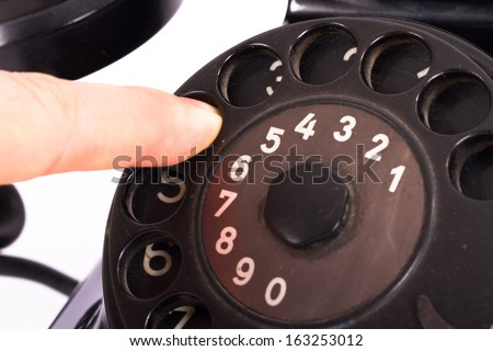 Close up view, hand finger on rotary dial of black vintage phone, isolated on white background. - stock photo