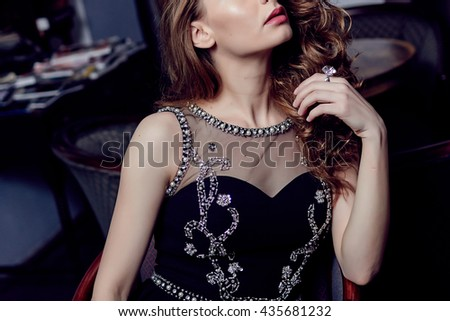 Close up view of a beautiful woman wearing a black dress and red lipstick  - stock photo