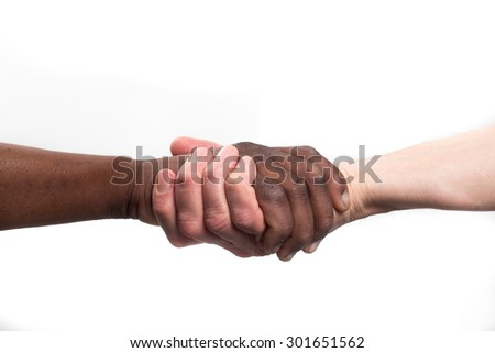 Close up view of a black / african man and a white / caucasian man shaking hands from below - stock photo