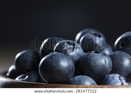 Close up view of a bowl of blueberries sitting on a rustic wooden table.