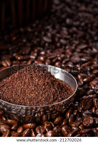 Close-up view of a bowl of fresh ground coffee laying on a bed of roasted whole, unground coffee beans - stock photo