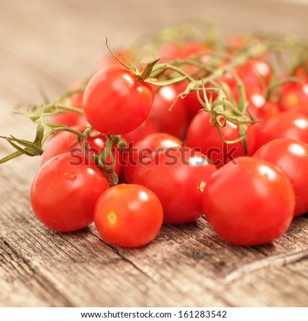 Close up view of a bunch of succulent ripe red cherry tomatoes on the vine on a rustic rough wooden with shallow dof - stock photo