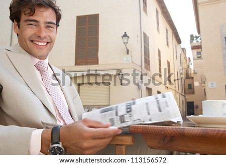 Close up view of a businessman reading the newspaper while having a coffee in a coffee shop terrace. - stock photo